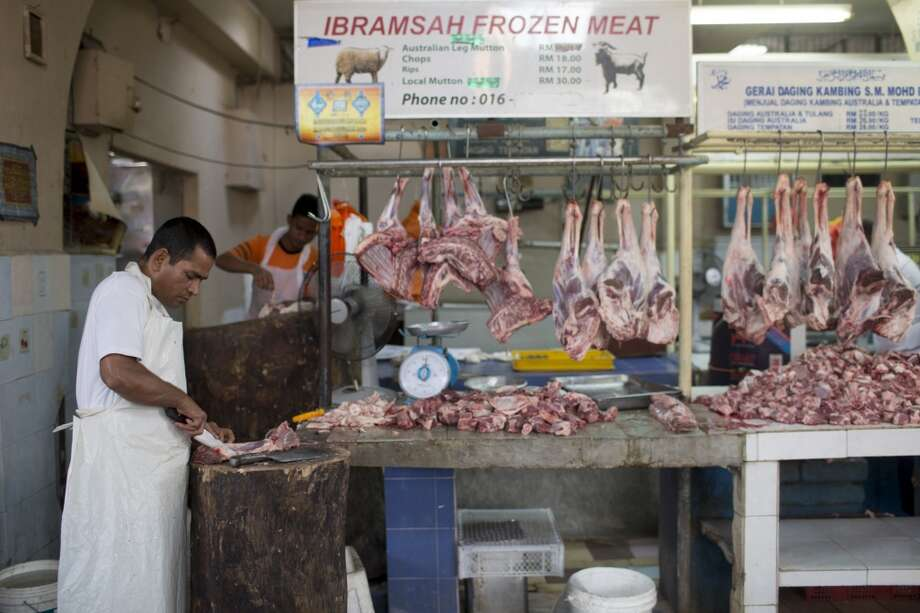 Malaysia: A vendor slices mutton at the Chow Kit wet market in Kuala Lumpur, Malaysia, on Tuesday, July 22, 2014. Photo: Brent Lewin, Bloomberg