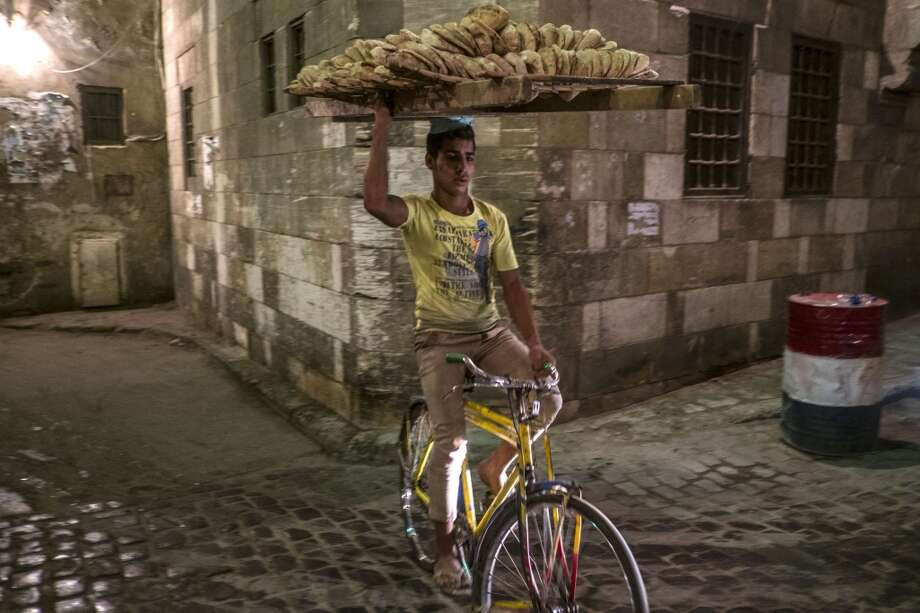 Egypt: An Egyptian bread seller rides his bicycle as Muslim worshipers break the day-long fast during the holy month of Ramadan in Cairo's Khan el-Khalili district . Photo: KHALED DESOUKI, AFP/Getty Images