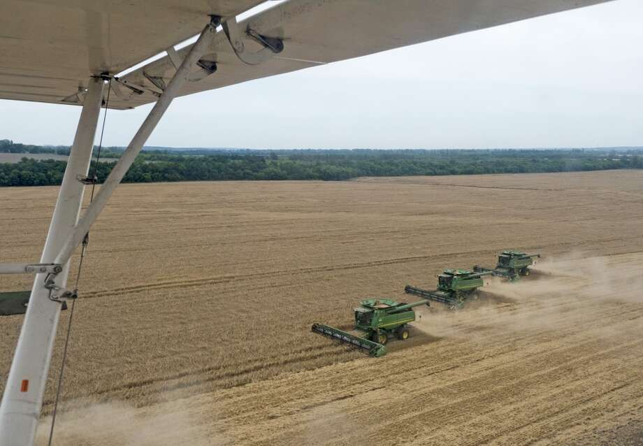 Ukraine': Multiple Deere & Co. combine harvesters drive across a wheat field operated by Ukrlandfarming Plc during a summer grain harvest seen from an aircraft in Poltava region, Ukraine. Photo: Vincent Mundy, Bloomberg