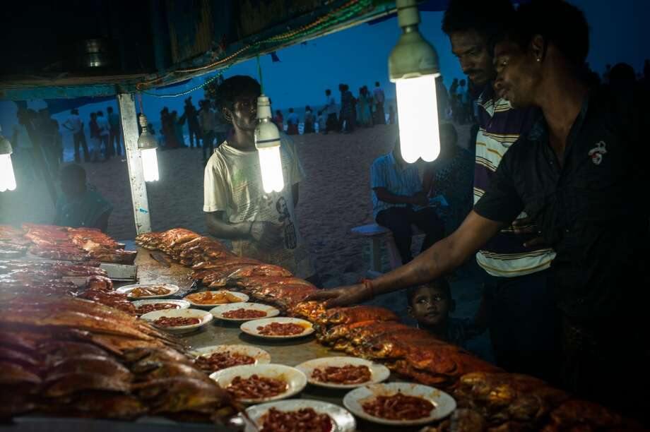 India: A vendor displays a selection of fish at a food stall on Marina Beach in Chennai, Tamil Nadu, India, on Sunday, July 20, 2014. Photo: Sanjit Das, Bloomberg