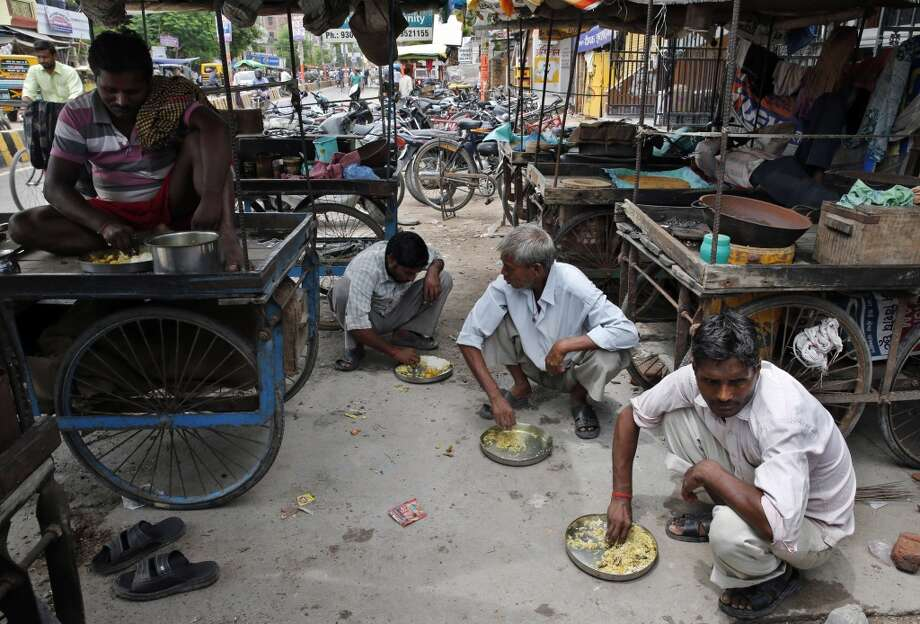 India: In this Thursday, July 24, 2014 photo, Indian street vendors eat a meal before starting their day's work in Allahabad, India. About 25 street food vendors live in this area sharing a single room to store their utensils while they sleep on their carts and on footpaths, earning about Rupees 5000- 7000 (US$ 85- 120) a month. Photo: Rajesh Kumar Singh, Associated Press