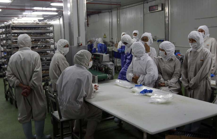 China: In this July 20, 2014 photo released by China's Xinhua News Agency, workers gather while they have nothing to do at the workshop of Shanghai Husi Food Co., a meat supplier for McDonald and KFC owned by OSI Group, a privately-held company that's based in Aurora, Ill. OSI was thrust into the spotlight this weekend when a Chinese TV station reported the Husi plant repackaged old beef and chicken and slapped new expiration dates on them. Photo: Pei Xin, Associated Press