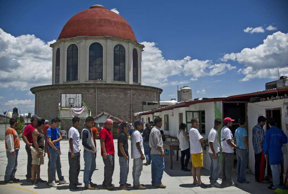 Mexico: Central American migrants wait in line for food at the Sagrada Familia shelter as they wait for the so-called La Bestia (The Beast) cargo train, in an attempt to reach the US border, in Apizaco, Tlaxcala state, Mexico on July 22, 2014. Photo: RONALDO SCHEMIDT, AFP/Getty Images