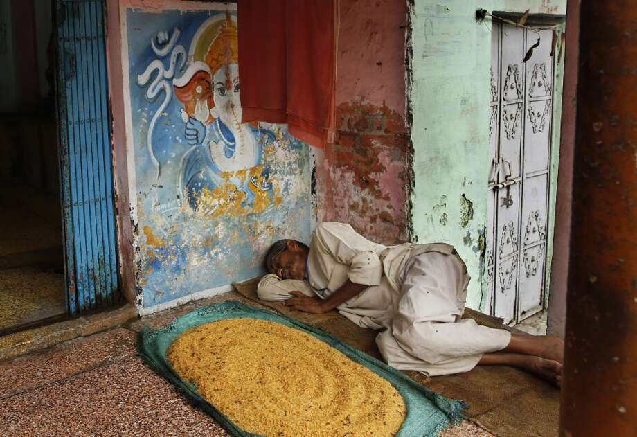 India: An Indian street vendor sleeps by grains of rice spread out to remove moisture in Allahabad, India. Photo: Rajesh Kumar Singh, Associated Press