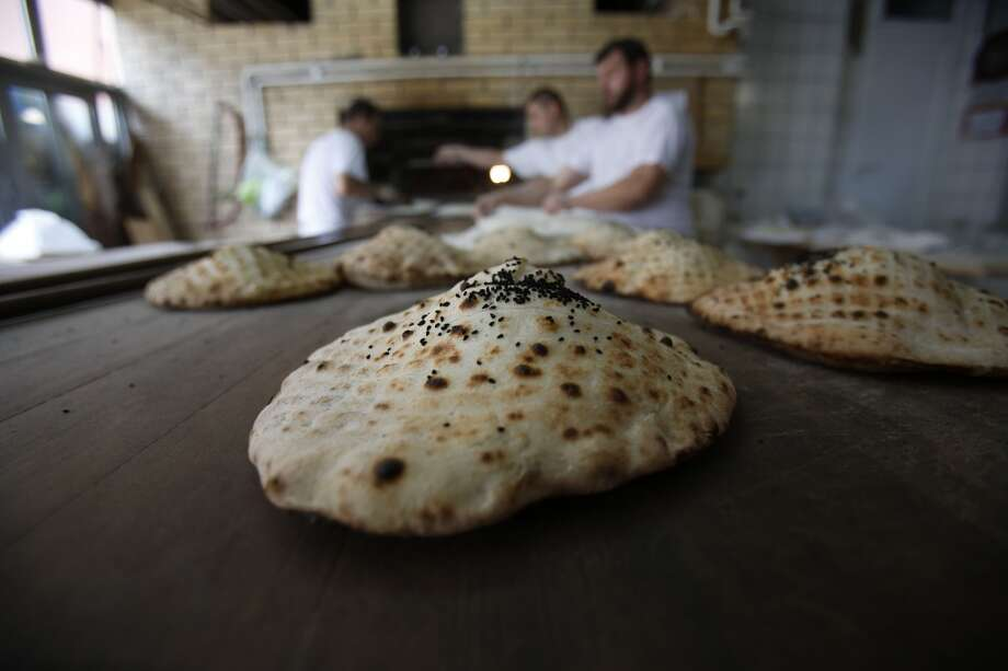 Bosnia: Agroup of bakers are seen preparing somun. All year around, bakeries in the Bosnian capital Sarajevo prepare the somun bread, served with many of the country's traditional meals. But it is only for Ramadan that bakers sprinkle the somun dough with black cumin seeds that release an aromatic smell when baked in wood burning ovens. Photo: AP, Associated Press