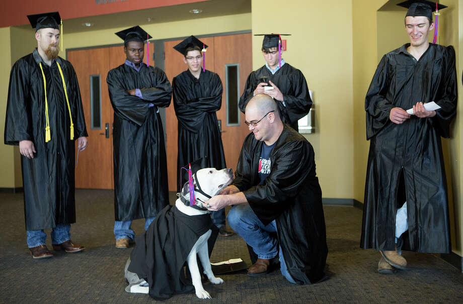Kolby Thompson, right, prepares his specially trained psychiatric service dog, Thor's, cap and gown before a graduation ceremony at Fallbrook Church, Friday, July 25, 2014, in Houston. Kolby is an Iraq, Afghanistan, Korea, Kuwait, Fort Bragg and Fort Bliss veteran who now lives with PTSD. Thor helps mitigate his stress. Photo: Cody Duty, Houston Chronicle / © 2014 Houston Chronicle