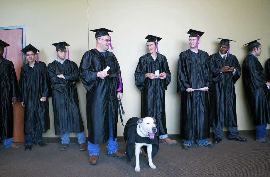 Kolby Thompson and his specially trained psychiatric service dog Thor, wait outside before a graduation ceremony at Fallbrook Church, Friday, July 25, 2014, in Houston. Kolby is an Iraq, Afghanistan, Korea, Kuwait, Fort Bragg and Fort Bliss veteran who now lives with PTSD. Thor helps mitigate his stress. Photo: Cody Duty, Houston Chronicle / © 2014 Houston Chronicle