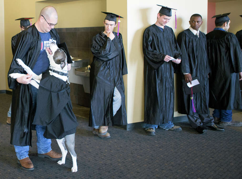 Kolby Thompson, left, and his specially trained psychiatric service dog Thor, wait outside before a graduation ceremony at Fallbrook Church, Friday, July 25, 2014, in Houston. Kolby is an Iraq, Afghanistan, Korea, Kuwait, Fort Bragg and Fort Bliss veteran who now lives with PTSD. Thor helps mitigate his stress. Photo: Cody Duty, Houston Chronicle / © 2014 Houston Chronicle