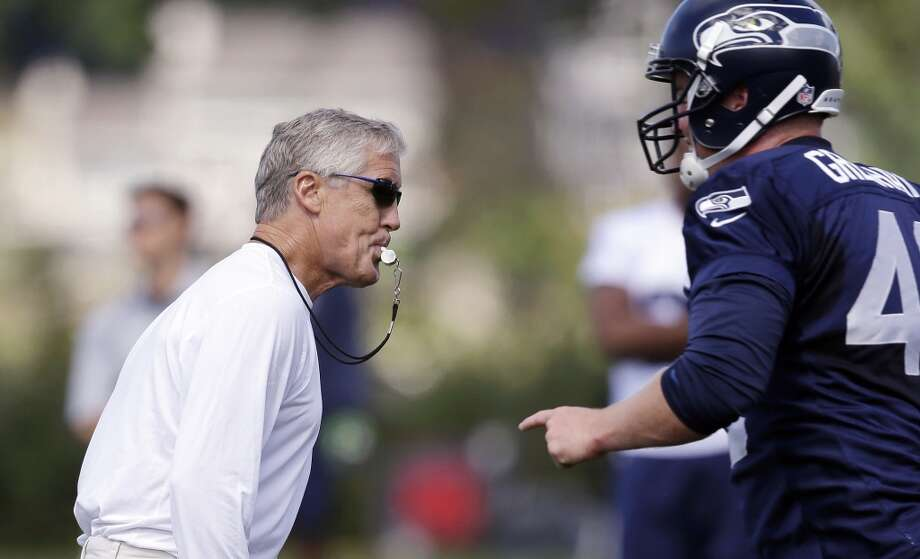 Seattle Seahawks head coach Pete Carroll, left, whistles the play stopped at an NFL football camp practice Friday. Photo: Associated Press