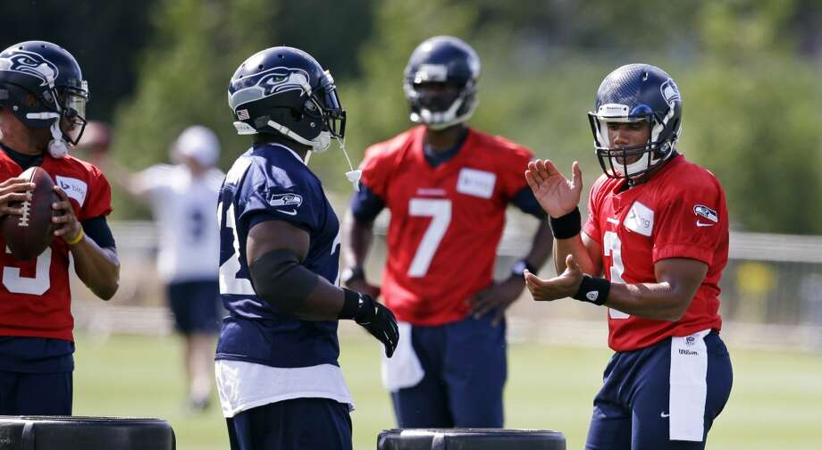 Seattle Seahawks' Russell Wilson, right, applauds the efforts of Robert Turbin as Wilson stands with other quarterbacks at an NFL football camp practice Friday. Photo: Associated Press