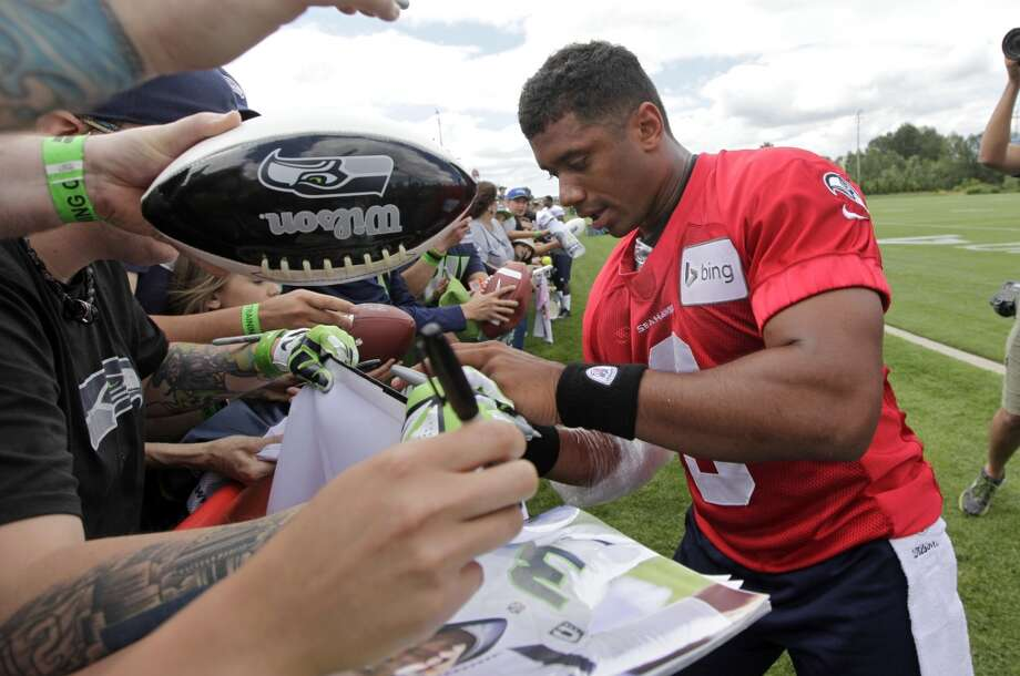 Seattle Seahawks quarterback Russell Wilson signs autographs following an NFL football camp practice Friday. Photo: Associated Press