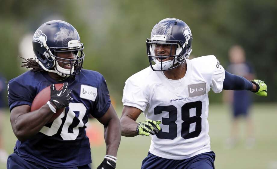 Seattle Seahawks' Demitrius Bronson, left, is chased by Chandler Fenner at an NFL football camp practice Friday. Photo: Associated Press