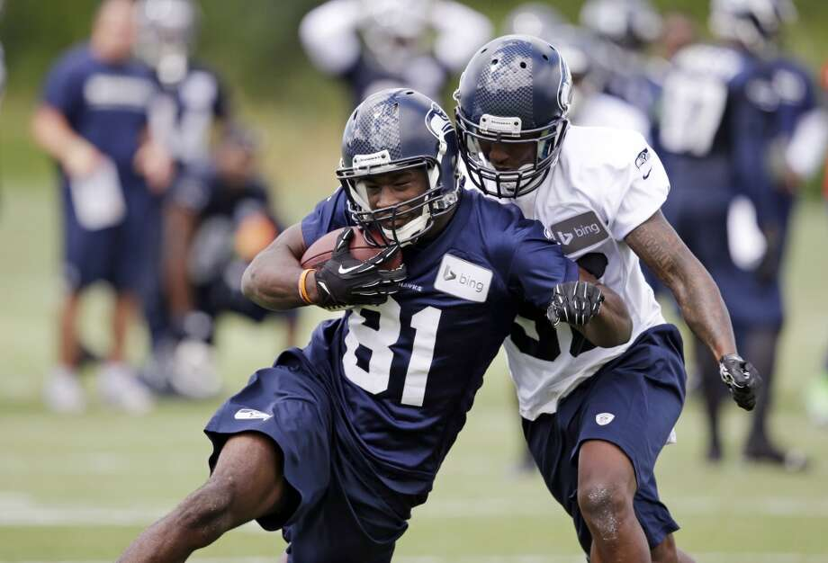 Seattle Seahawks' Kevin Norwood (81) tries to hold onto the ball as Akeem Auguste comes in from behind to try and knock it away at an NFL football camp practice Friday. Photo: Associated Press