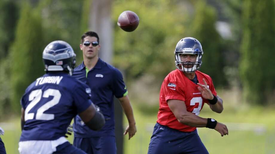Seattle Seahawks quarterback Russell Wilson, right watches the path of his throw to Robert Turbin at an NFL football camp practice Friday. Photo: Associated Press