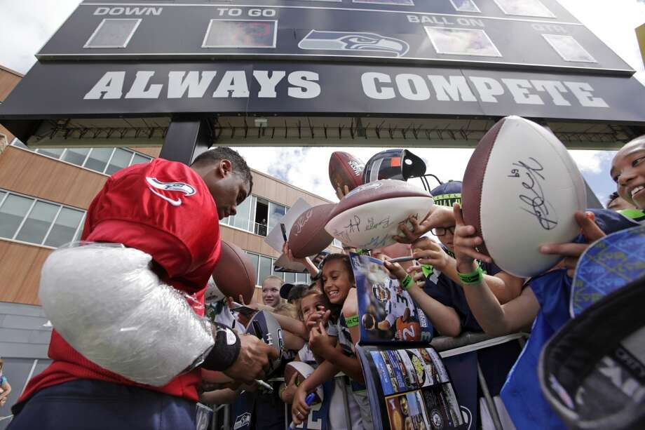 With his throwing arm wrapped in ice, Seattle Seahawks quarterback Russell Wilson signs autographs beneath a scoreboard that includes the team's slogan following an NFL football camp practice on Friday. Photo: Associated Press