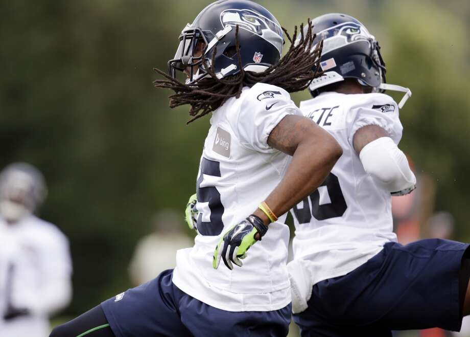 Seattle Seahawks cornerbacks Richard Sherman, left, and Akeem Auguste leap back-to-back as they celebrate a defensive play at an NFL football camp practice Friday. Photo: Associated Press