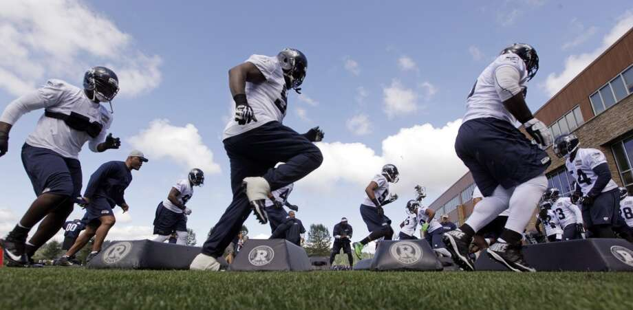 Seattle Seahawks players run through a drill at the first day NFL football training camp on Friday. Photo: Associated Press