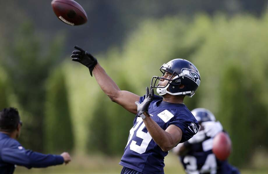 Seattle Seahawks' Doug Baldwin tosses back a football after a reception and run at an NFL football camp practice Friday. Photo: Associated Press