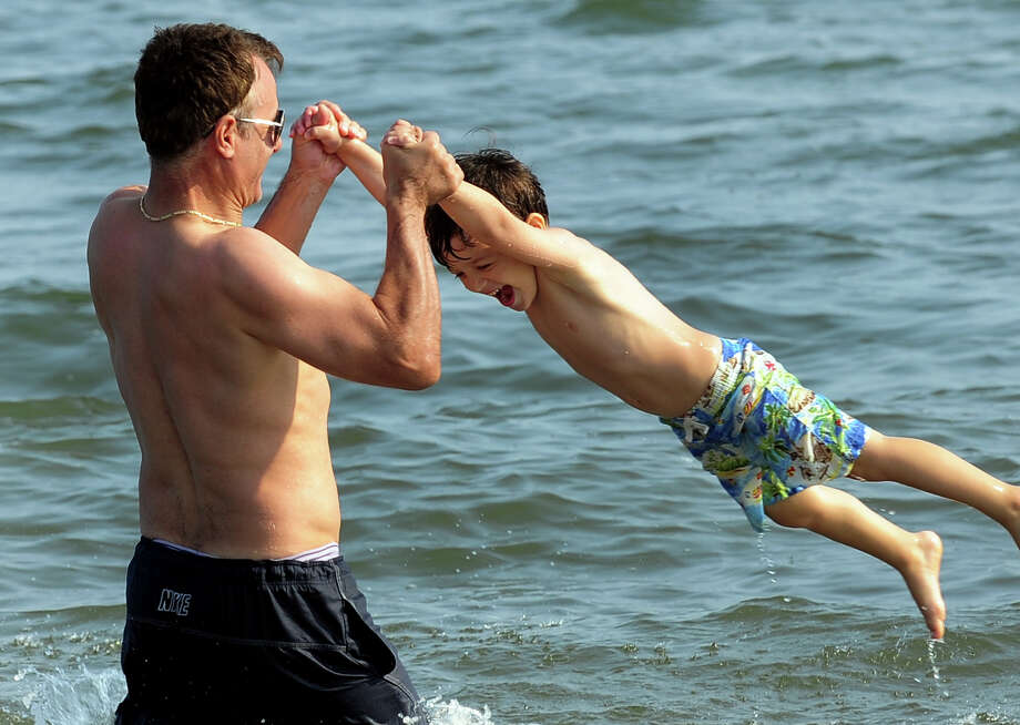 Andy Balliu, of NYC, spins his son Arber, 4, around in the water as he enjoys time with his family at Silver Sands State Park in Westport, Conn. on Friday July 25, 2014. Photo: Christian Abraham / Connecticut Post