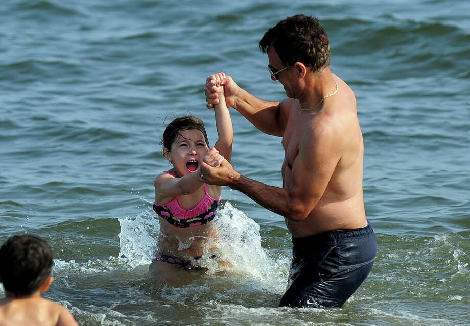 Andy Balliu, of NYC, spins his daughter Livia, 6, around in the water as he enjoys time with his family at Silver Sands State Park in Westport, Conn. on Friday July 25, 2014. Photo: Christian Abraham / Connecticut Post