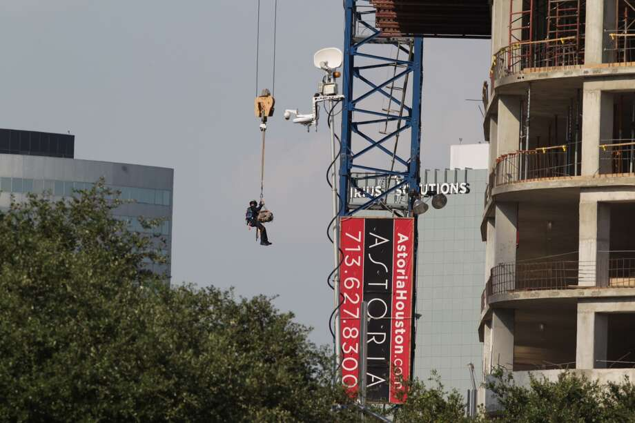 Houston Fire Department crews use a crane to rescue an injured construction worker high above the ground in the Galleria area. James Nielsen / Houston Chronicle Photo: James Nielsen, Houston Chronicle