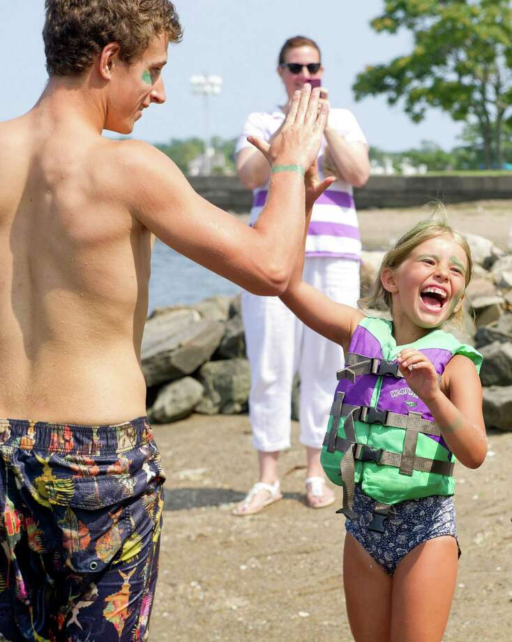 "Masha Selman, 6, gets a big high-five from a counselor after her team, the Sea Stars, won Camp SoundWaters' ""Anything That Floats"" boat race at Cove Island Park in Stamford, Conn., on Friday, July 25, 2014. Photo: Lindsay Perry / Stamford Advocate"