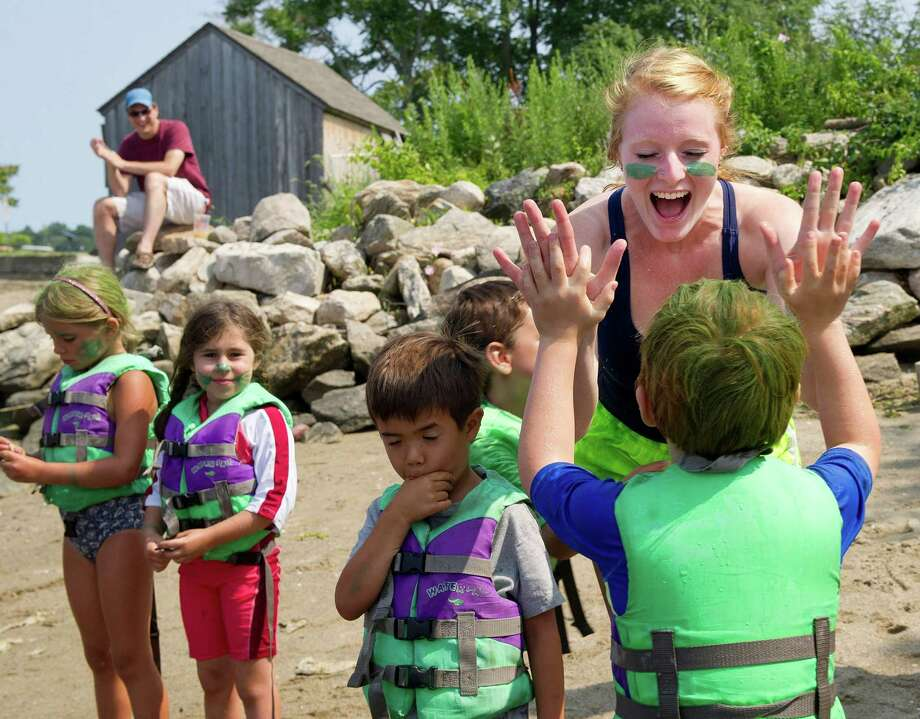 "Counselor Julia Simpson gives out high-fives to the Sea Stars after their team won Camp SoundWaters' ""Anything That Floats"" boat race at Cove Island Park in Stamford, Conn., on Friday, July 25, 2014. Photo: Lindsay Perry / Stamford Advocate"
