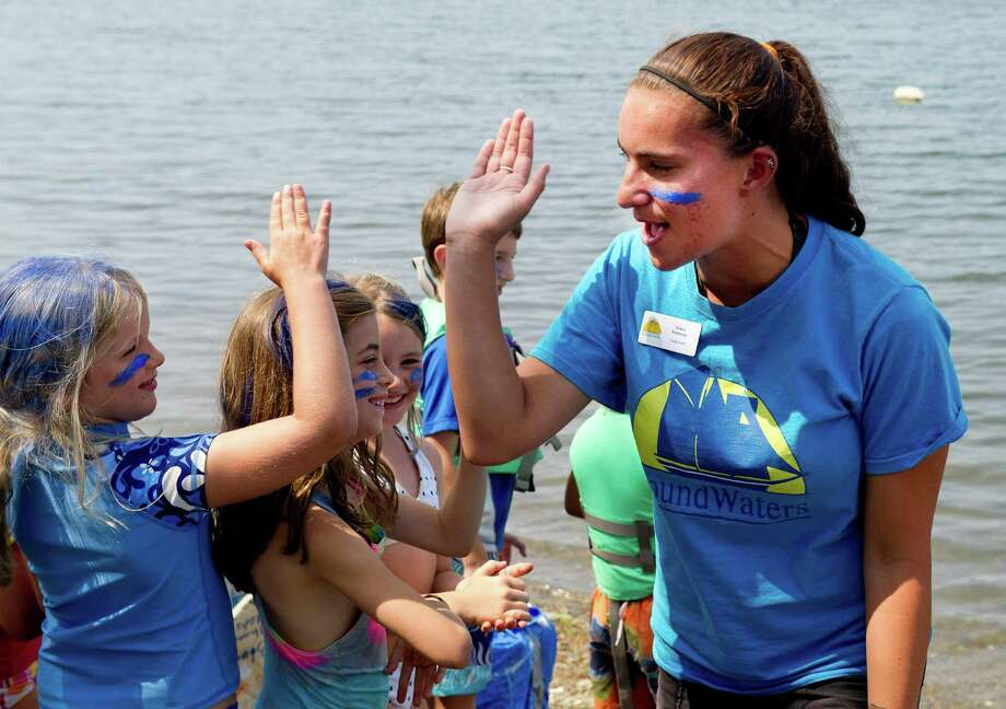"""Counselor Kiara Kallaway gives out high-fives during Camp SoundWaters' """"Anything That Floats"""" boat race at Cove Island Park in Stamford, Conn., on Friday, July 25, 2014. Photo: Lindsay Perry / Stamford Advocate"""
