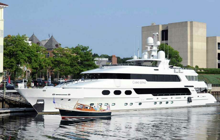 A motorboat, foreground, cruises past the 163-foot, 4- inch long mega-yacht, Casino Royale, dockside at the Delamar Hotel, Greenwich Harbor, Conn., Friday evening, July 25, 2014. An online search says it is was purchased in 2009 by retired California businessman David McDonald.  The yacht was reportedly named by its first owner after Ian FlemingâÄôs James Bond novel. Photo: Bob Luckey / Greenwich Time