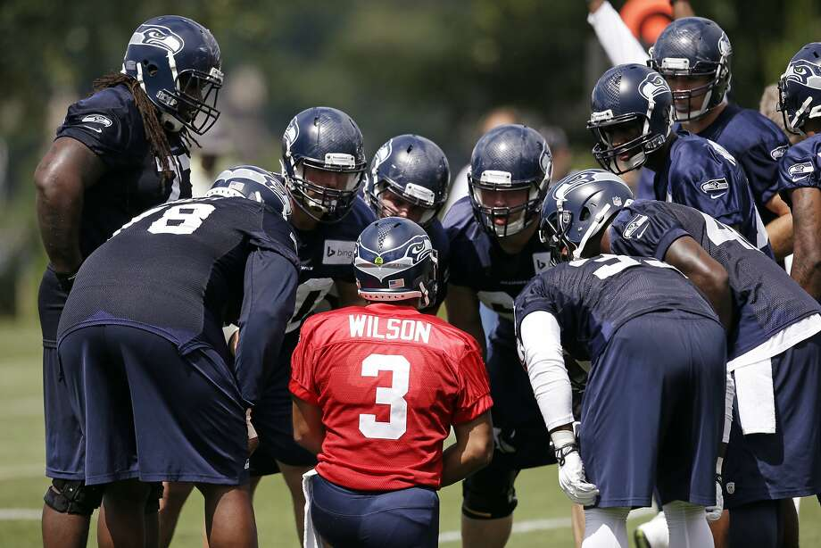 Russell Wilson huddles with teammates - none of whom were Marshawn Lynch - during the Seahawks' first practice. Photo: Associated Press