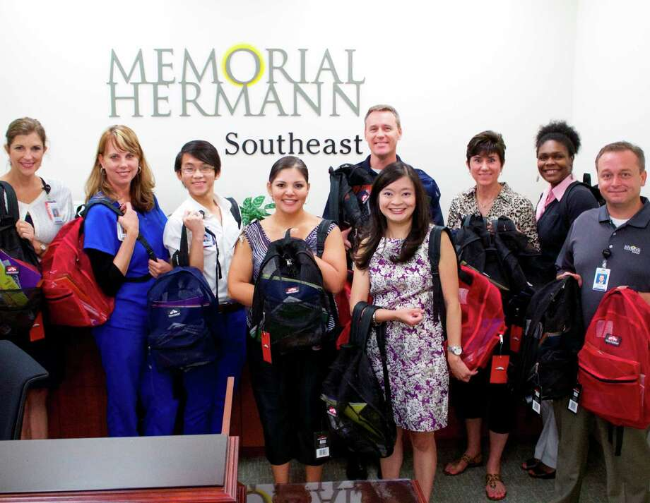 Memorial Hermann Southeast Hospital employees Rebecca Lilley, left, Mindy Rivera, Son Dinh, Lydia Garcia, Michael Collins, chief executive officer Erin Asprec, Lori Gordon, Kizzy Thomas and Glenn Burnett, donate new backpacks filled with school supplies for Operation Backpack. Photo: Ariana Montelongo / Memorial Hermann Southeast Hospital
