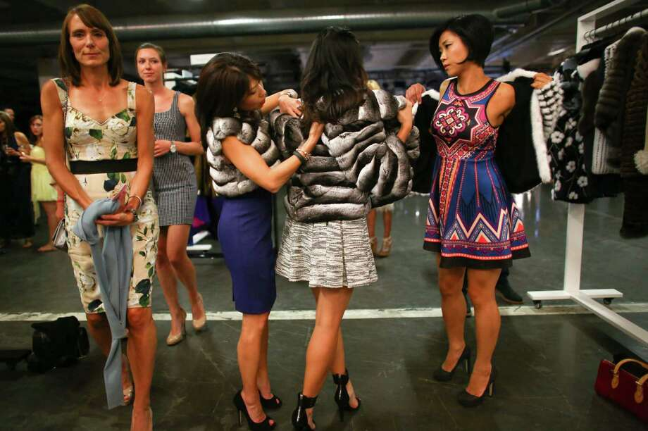 "Susan Kim, Lina Kim and Jaime Han, right, try on coats during the annual Nordstrom Designer Preview fashion show at Smith Cove Event Center at Pier 91 in Seattle. The event helped raise funds for Seattle Art Museum and incorporated elements of  the Museum's upcoming exhibit ""Pop Departures"" into the show. Photographed on Thursday, July 24, 2014. Photo: JOSHUA TRUJILLO, SEATTLEPI.COM / SEATTLEPI.COM"