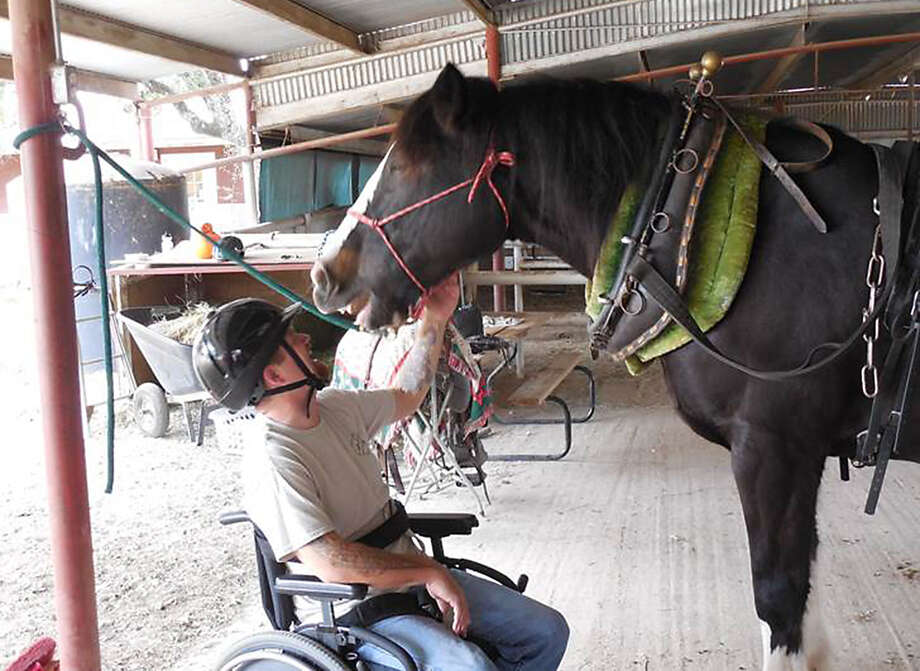Curt Oswalt, a wounded warrior, gives Daisy some attention after a ride at Triple H Equitherapy Center in Pipe Creek. Photo: Courtesy