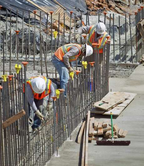 Construction workers clean and straighten rebar so it will bond when the concrete is poured on the University of Houston's new on-campus stadium, Tuesday, June 25, 2013, in Houston. ( Nick de la Torre / Houston Chronicle ) Photo: Nick De La Torre, Staff / Â 2013  Houston Chronicle