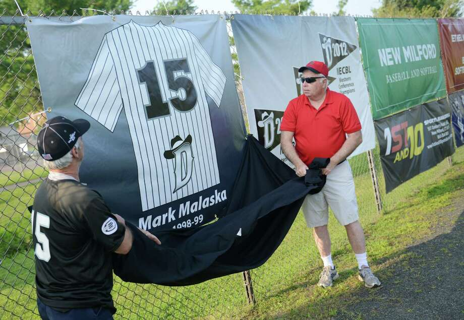 Longtime fan John Consentino, left, and Danbury Westerners Chief Operating Officer Mike Malone unveil the jersey of Westerners legend Mark Malaska as the team retires his number 15 before the Westerners' game against the Ocean State Waves at Rogers Park in Danbury, Conn. Friday, July 25, 2014.  Malaska holds many franchise single-season batting records from his two seasons with the Westerners in 1998 and 1999 and was inducted into the NECBL Hall of Fame in 2010 as a member of its introductory class. Photo: Tyler Sizemore / The News-Times