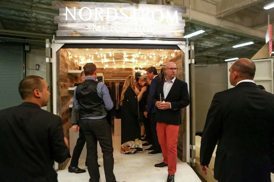 """Guests gather in the Men's Shop, a converted shipping container during the annual Nordstrom Designer Preview fashion show at Smith Cove Event Center at Pier 91 in Seattle. The event helped raise funds for Seattle Art Museum and incorporated elements of  the Museum's upcoming exhibit """"Pop Departures"""" into the show. Photographed on Thursday, July 24, 2014. Photo: JOSHUA TRUJILLO, SEATTLEPI.COM / SEATTLEPI.COM"""