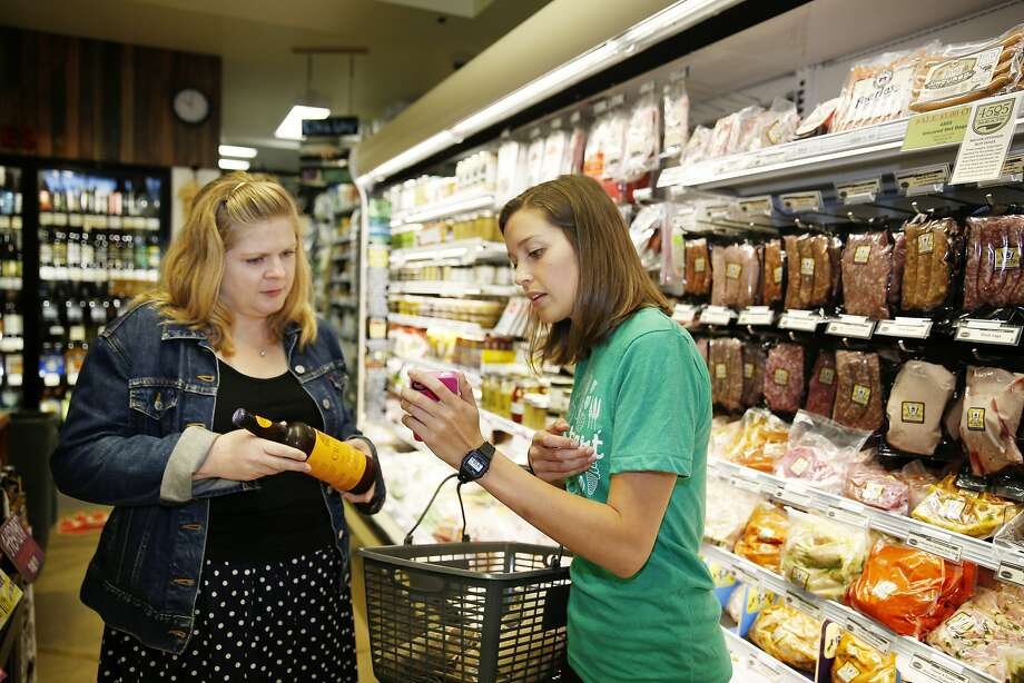 Instacart personal shopper, Sydney Hollingsworth (right), consults with Jessie Rogers (left), Bi-Rite marketing director, as she tries to find a product on a customer's order at the Bi-Rite Market on Divisadero Street on Thursday, July 24,  2014 in San Francisco, Calif. Photo: Lea Suzuki, The Chronicle