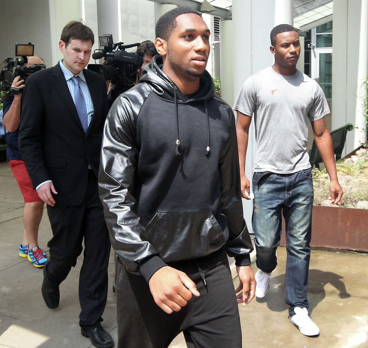 UT football players Kendall Sanders, left, and Montrel Meander, right, leave the Travis County Criminal Justice Center after being booked Thursday.