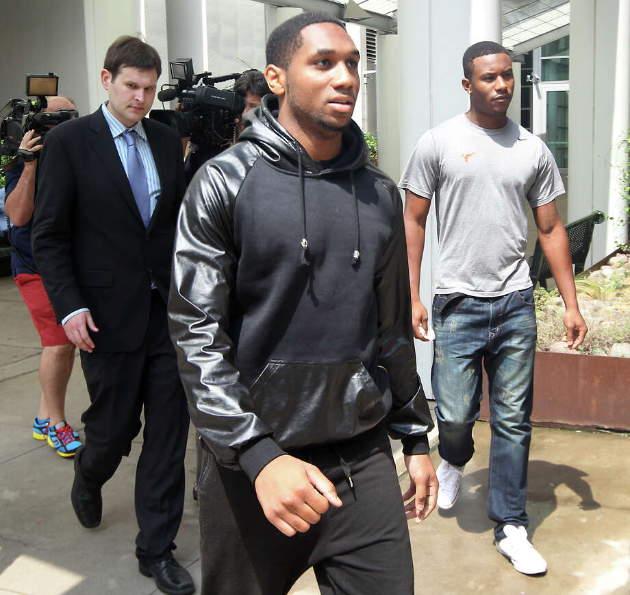 UT football players Kendall Sanders, left, and Montrel Meander, right, leave the Travis County Criminal Justice Center after being booked Thursday.  Photo: Ralph Barrera, MBO / Austin American-Statesman