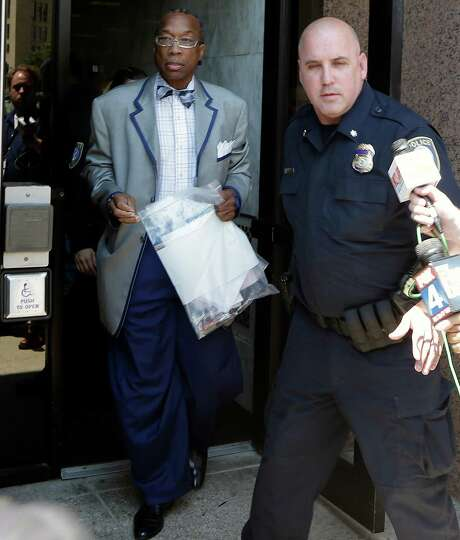 Dallas County Commissioner John Wiley Price, left, leaves the federal courthouse in Dallas on Friday, July 25, 2014. Federal authorities charged Price with accepting nearly $1 million in bribes in exchange for providing insider information and voting in favor of certain projects. (AP Photo) Photo: STF / AP
