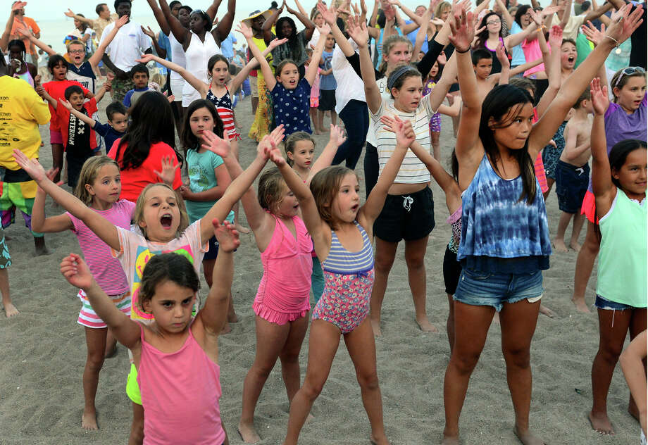 """Kids dance to Y.M.C.A. at the Sand Jam and Family Movie Nights event at Jennings Beach in Fairfield, Conn. on Friday July 25, 2014. Music was provided by Paul Herman with Double Up Company and later when it got dark, kids and their families watched """"The Lego Movie."""" Photo: Christian Abraham / Connecticut Post"""