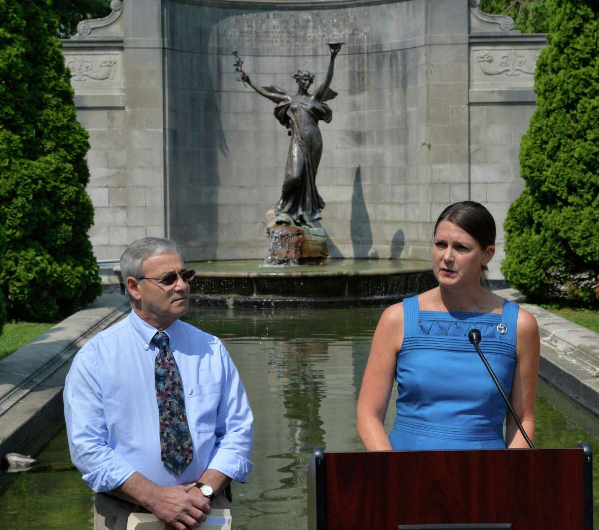 Samantha Mosshart, executive director of the Saratoga Springs Preservation Foundation, right, announces the renovation plans for memorial built in honor of Spencer Trask, background, in Congress Park Friday morning July 25, 2014 in Saratoga Springs, N.Y. Joining Bosshart is Anthony