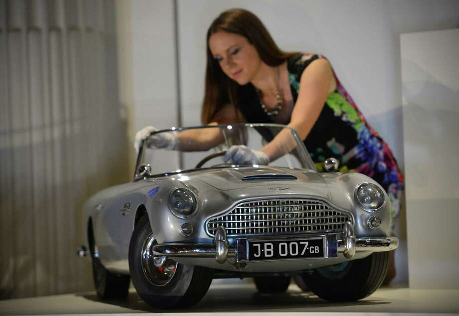 A member of staff poses for photographers with a miniature James Bond DB5 presented to Britain's Prince Andrew by the Aston Martin company in 1965, at Buckingham Palace in central London on July 24, 2014, during a preview for the forthcoming exhibition exploring 250 years of royal childhood. A special exhibition on childhood in the British royal family is to open at Buckingham Palace on Saturday, featuring well-loved toys spanning 250 years including a gadget-laden miniature James Bond supercar. Photo: CARL COURT, AFP/Getty Images / AFP