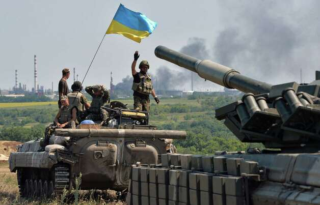 """An armoured personnel carrier flying Ukraine's flag (L) and a Ukrainian tank, from a convoy of the Ukrainian forces, drive towards the eastern Ukrainian city of Lysychansk, in the region of Lugansk, on July 25, 2014. Russia on Friday called the latest US accusations of Moscow's involvement in the Ukrainian conflict a baseless """"smear campaign"""" and said Washington bears responsibility for the bloodshed. AFP PHOTO / GENYA SAVILOVGENYA SAVILOV/AFP/Getty Images Photo: GENYA SAVILOV / Genya Savilov"""