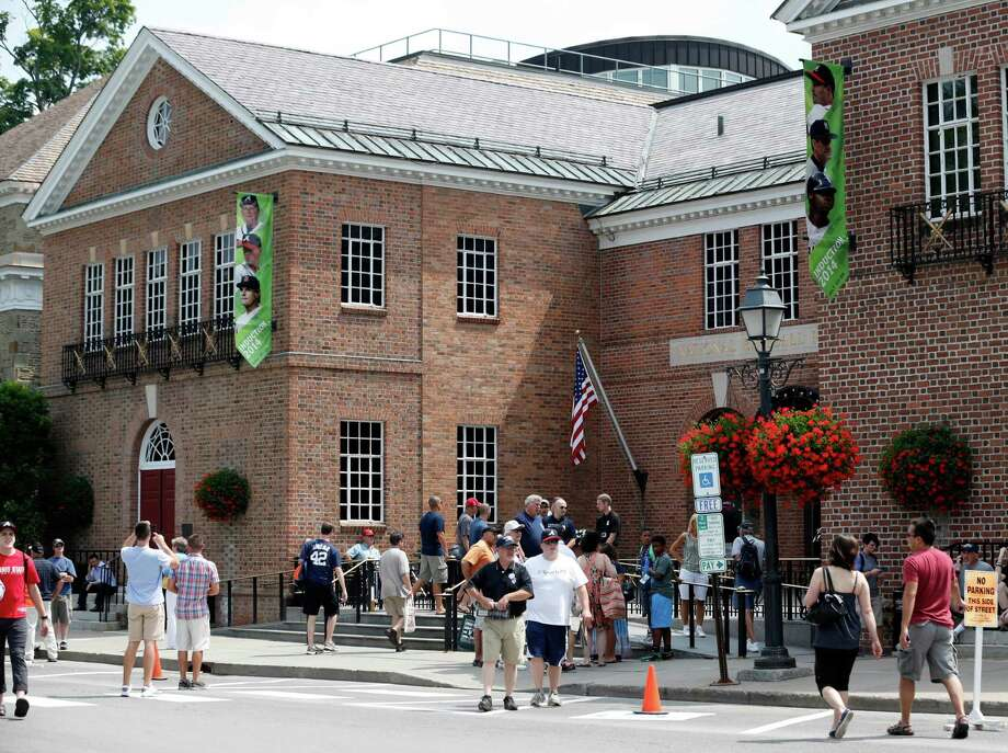 Fans walk outside the Baseball Hall of Fame and Museum on Friday, July 25, 2014, in Cooperstown, N.Y. Former Major League Baseball managers Joe Torre, Bobby Cox and Tony La Russa, with pitchers Greg Maddux and Tom Glavine and slugger Frank Thomas, will be inducted to the hall on Sunday. (AP Photo) ORG XMIT: NYMG101 / AP