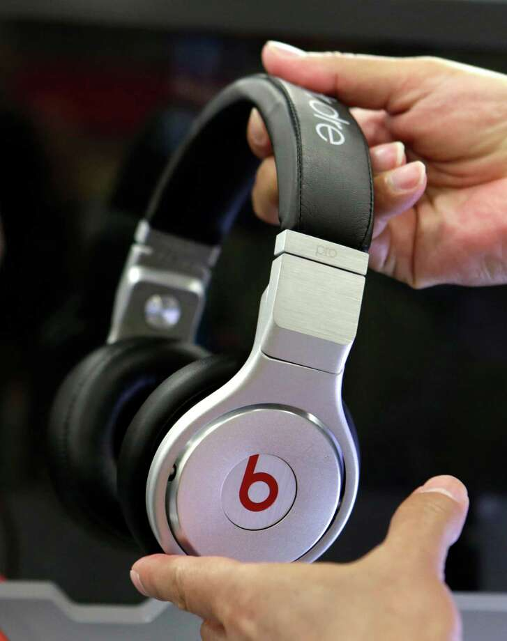 A customer holds a pair a Beats headphones at a Best Buy in Hialeah, Fla., in late May after Apple announced it was acquiring Beats Electronics. Photo: Alan Diaz, STF / AP