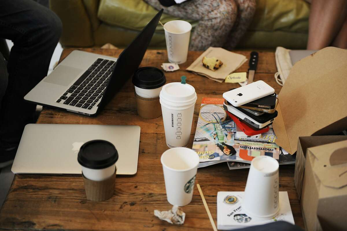 """Coffee and phones adorn the table during a meeting for Near Me employees at Makeshift Society in the Hayes Valley area on July 16, 2014 in San Francisco, CA. Near Me is a startup company with a """"just add water"""" platform for companies that want to be the """"Airbnb of X."""" Once a month, for a change of scenery, Near Me rents a bigger office space."""