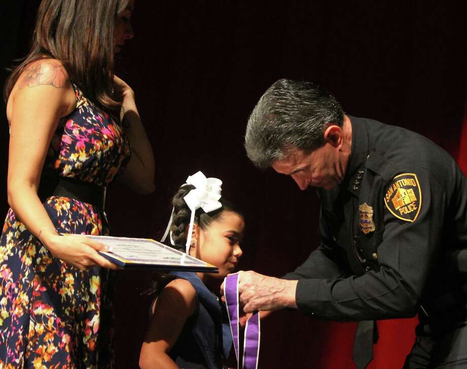 Officer Bobby Deckard's 7-year-old daughter, Cheyenne, and his widow, Denise, accept the Purple Heart Medal and the Medal of Valor from Police Chief William McManus. Deckard was shot in the head while chasing robbery suspects in his patrol car on Dec. 8 and died Dec. 20. Photo: Photos By Bria Webb / San Antonio Express-News / SAN ANTONIO EXPRESS-NEWS