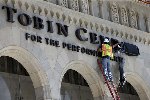 Brent Jordan uses a tall ladder as workers unveil the Tobin Center for the Performing Arts lettering above the entrance to the new building on July 25, 2014. Photo: TOM REEL