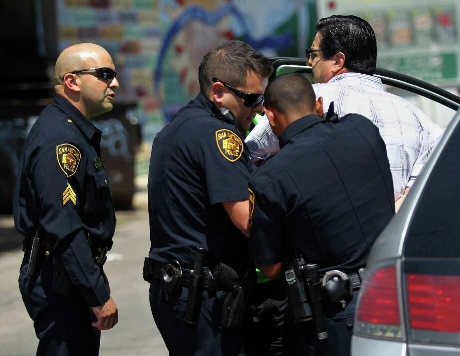 During a sting operation conducted Friday, SAPD officers arrest a man suspected of soliciting prostitution in the 500 block of San Patricio Street in San Antonio. Photo: Timothy Tai / San Antonio Express-News / © 2014 San Antonio Express-News